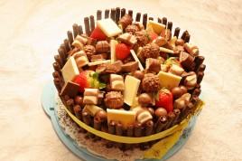 Tort de ciocolata cu crema de branza si decorat cu multe bomboane si capsuni